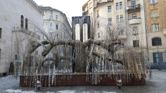 A weeping willow tree made of metal and in the upside-down style of the Menorah, the 7-candleholder in Jewish ceremonial tradition.